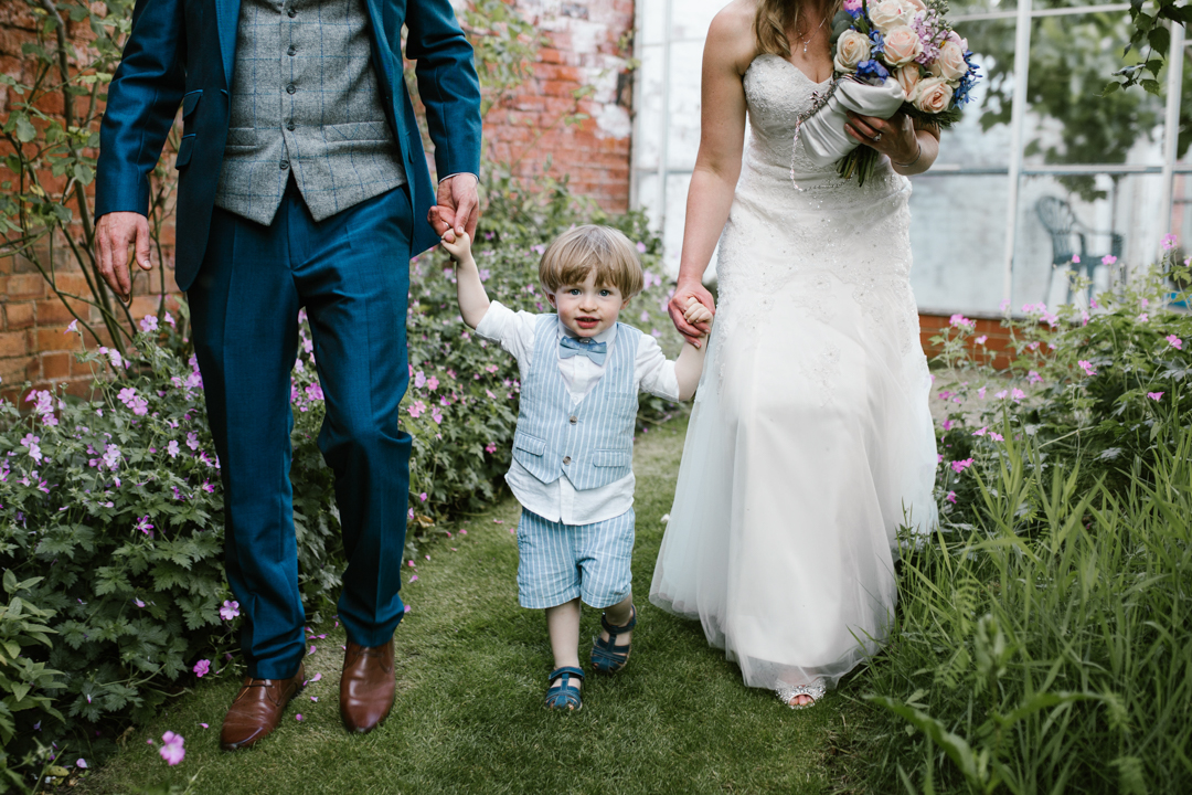son walking hand in hand with his mom and dad in the gardens of the walled garden- nottingham wedding