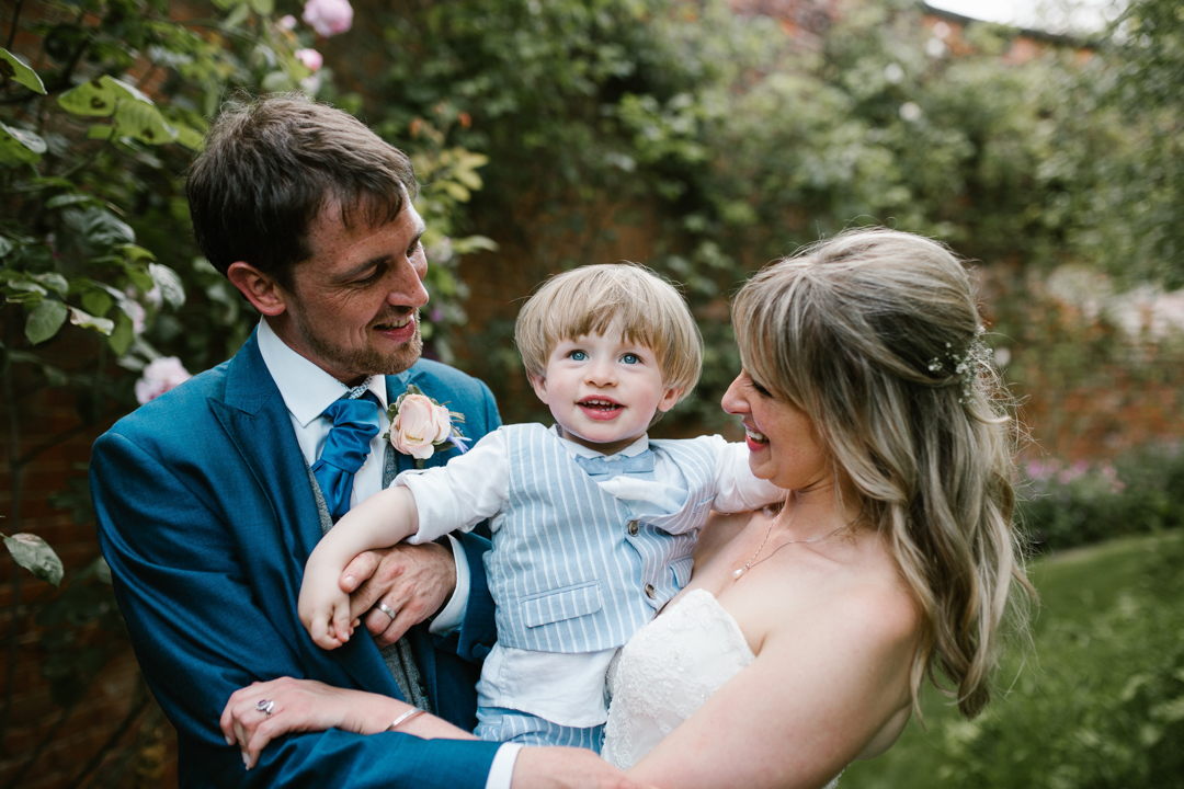 bride and groom holding their son smiling together in the walled garden - nottingham wedding
