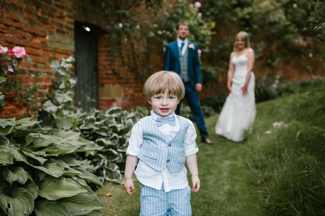son at his mom and dads wedding dressed in a blue suit