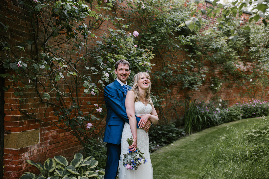 wife laughing out loud as her new husband hugs her from behind after their nottingham wedding