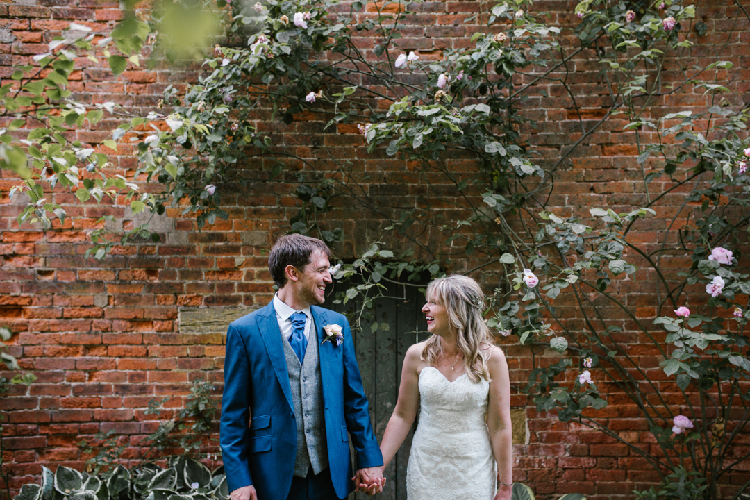 bride and groom holiding hands standing in front of a brick wall full of roses at the walled garden nottingham