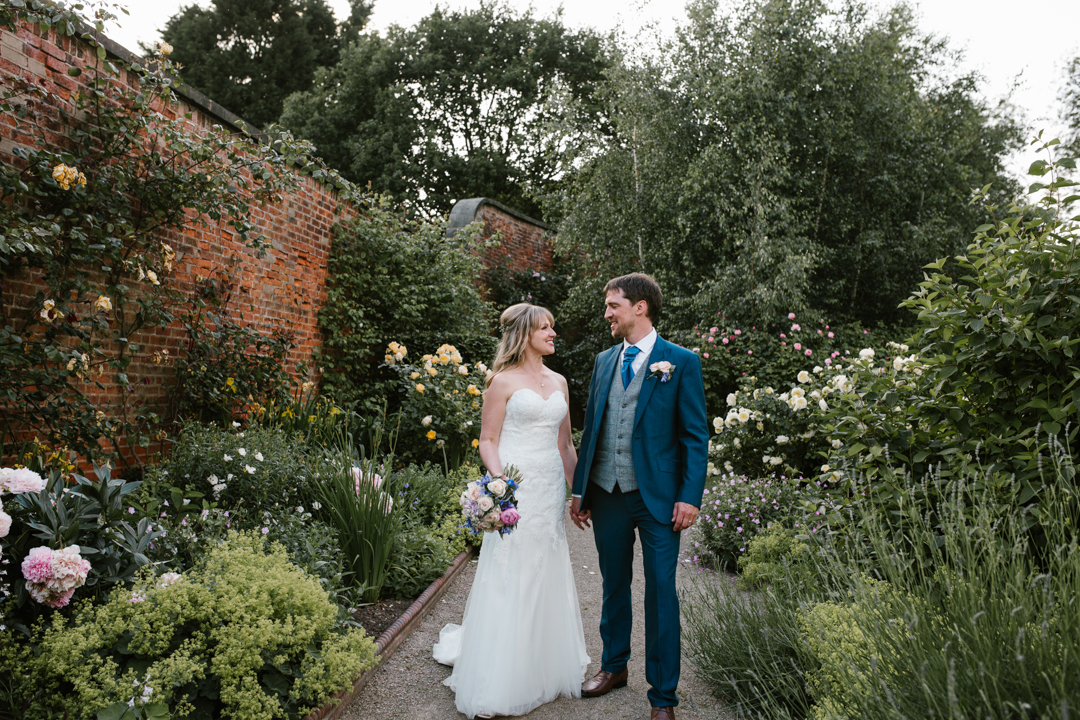 natural and bright photo of bride and groom standing next to one another in the walled garden at beeston fields nottingham