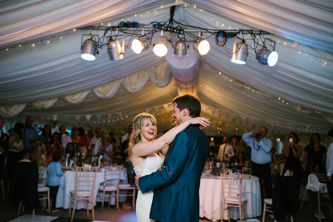 bride and groom in the centre of the dancefloor laughing together during their first dance