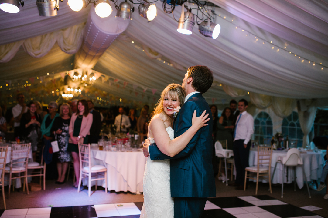 documentary photo of bride and groom hugging on the dance floor during their first dance at the walled garden beeston fields