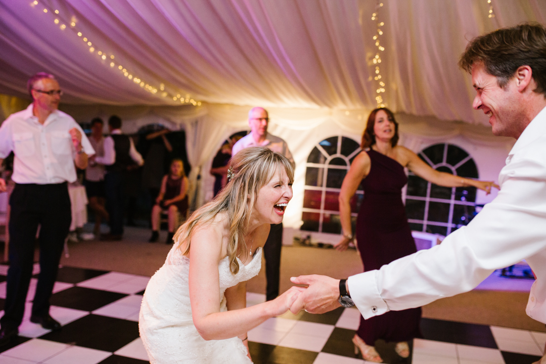 natural fun photo of bride laughing as she dances with one of her wedding guests at a fun wedding in nottingham