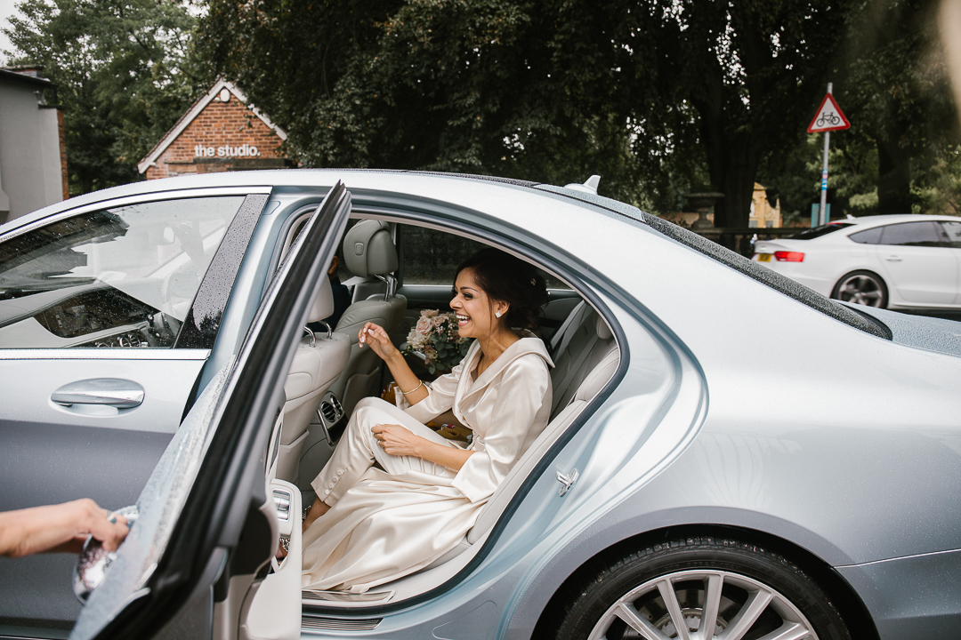 natural candid photo of bride getting out of the mercedes benz on the morning of her wedding