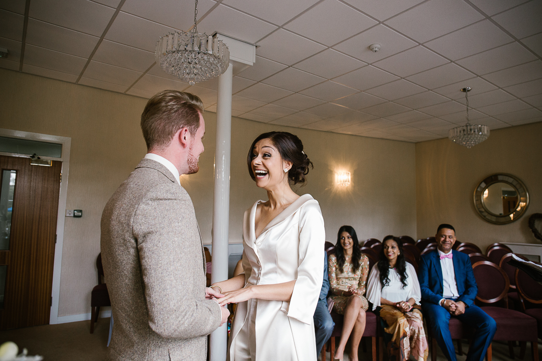 Birde laughing in Lichfield registry office during wedding vows