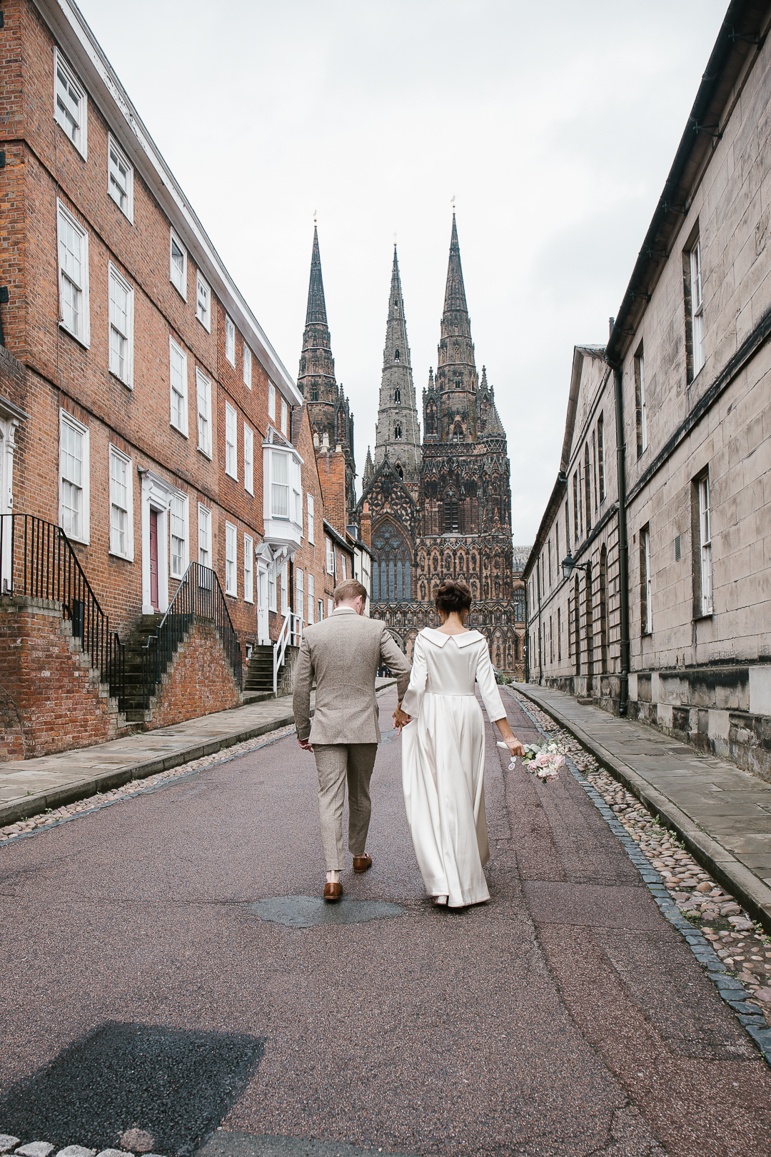 bride and groom walking towards lichfield cathedral after their intimate wedding in lichfield