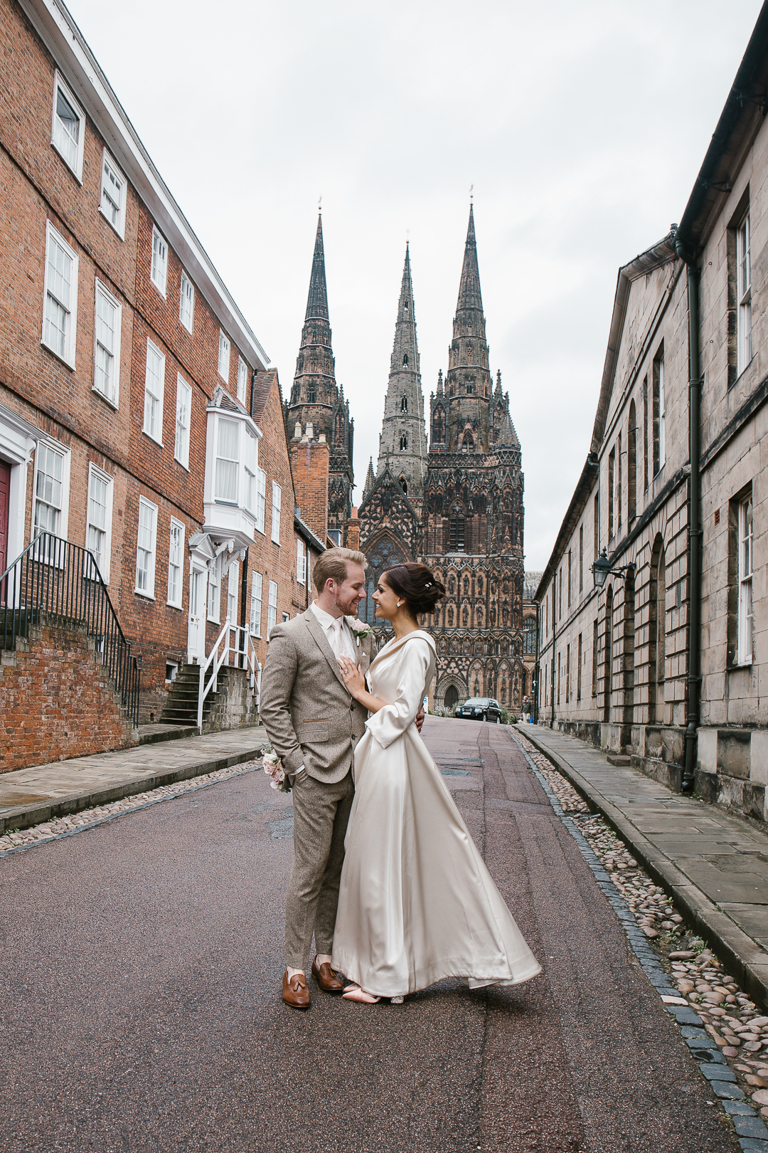 romantic photo of bride and groom smiling at one another with lichfield cathedral in the background
