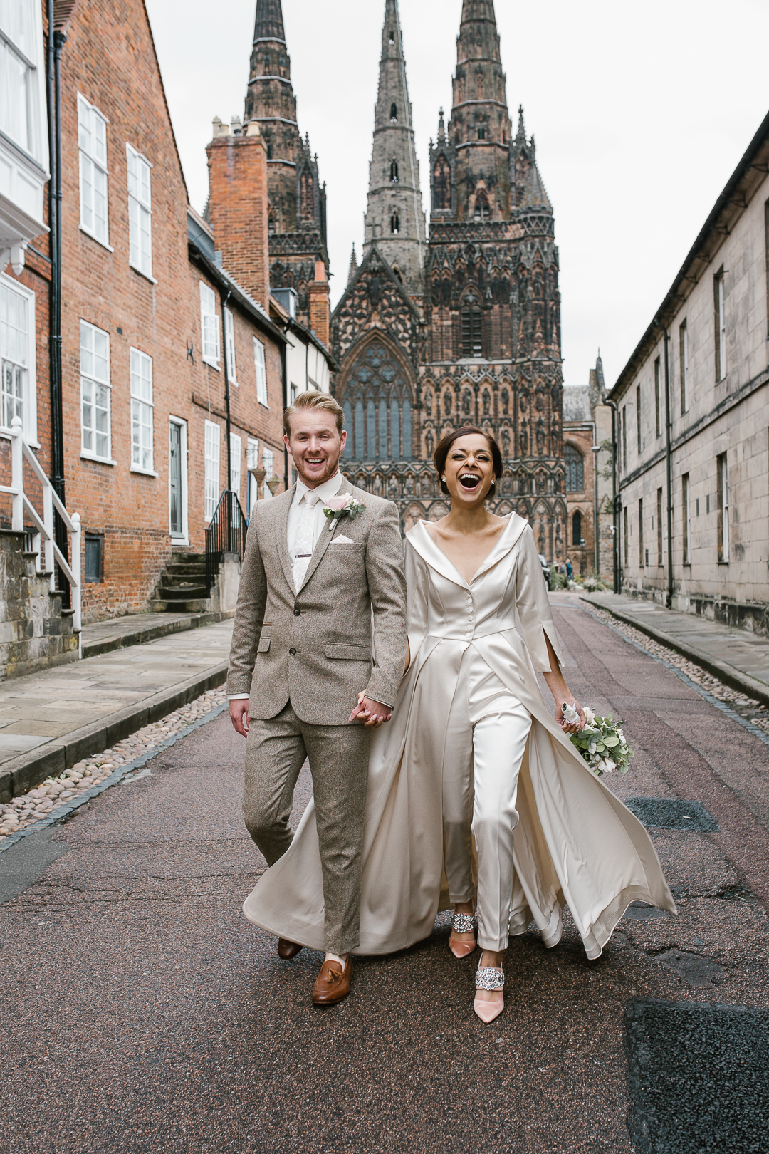 natural happy photo of bride and groom holding hands laughing with lichfield cathedral in the background- lichfield wedding photographer