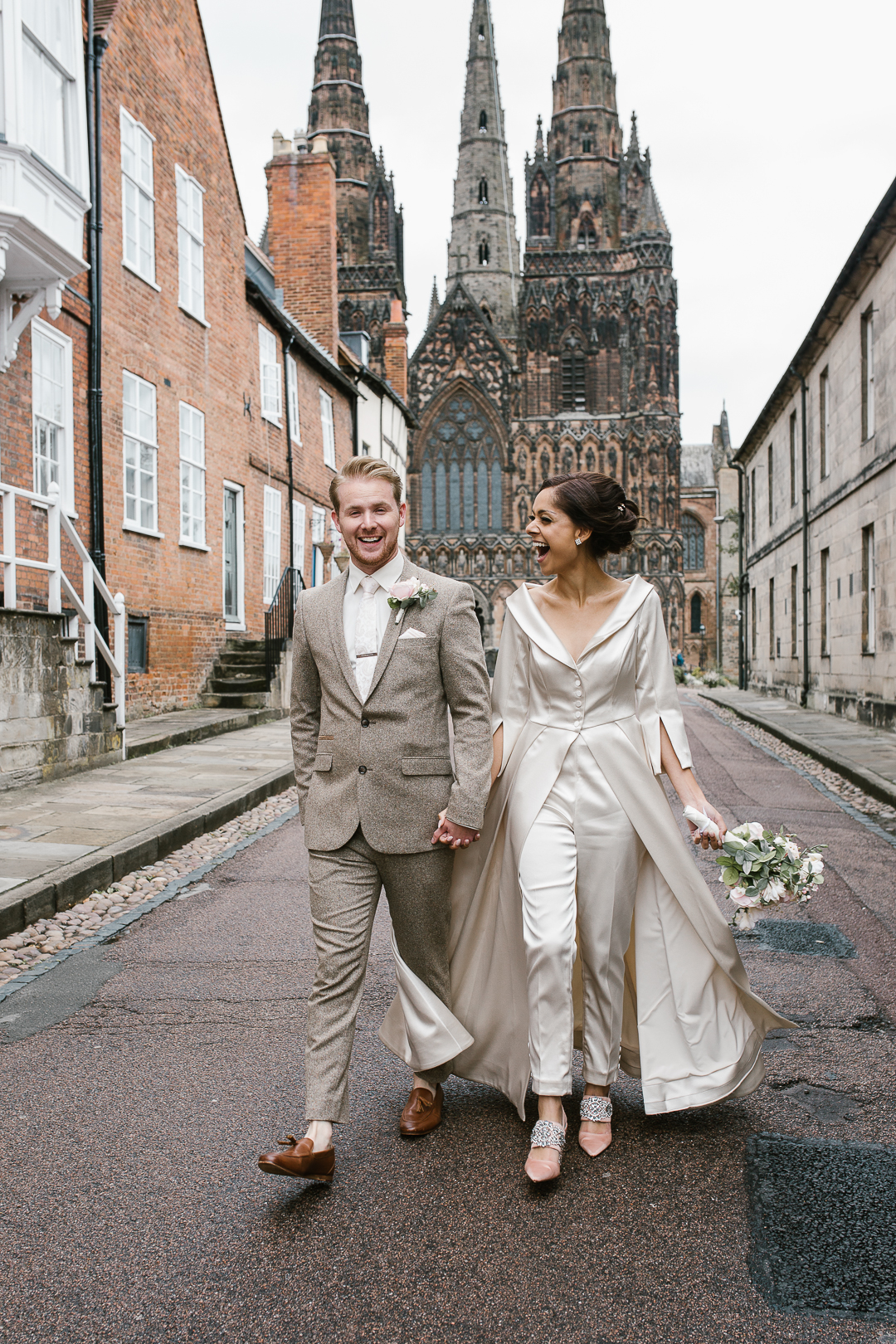natural photo of newlyweds walking hand in hand in lichfield- lichfield wedding