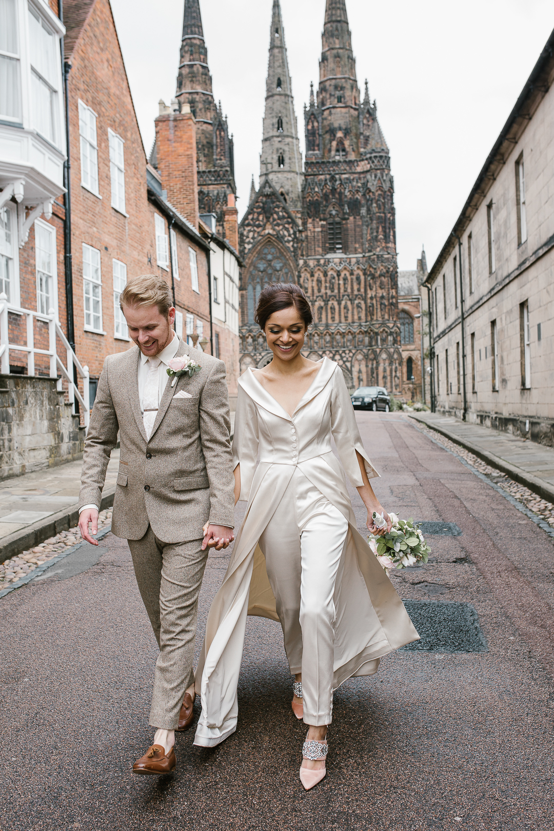 happy fun photo of bride and groom laughing infront of lichfield cathedral- natural wedding photographer in staffordshire