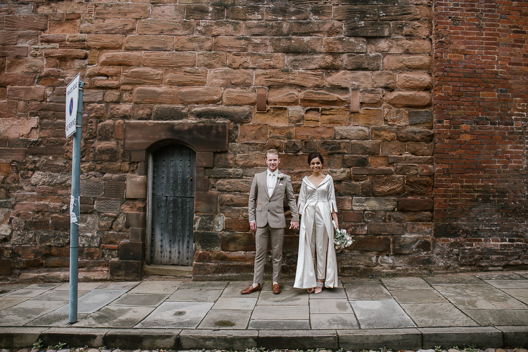 quirky photo of bride and groom standing in front of a brick wall in lichfield after their intimate wedding- lichfield wedding
