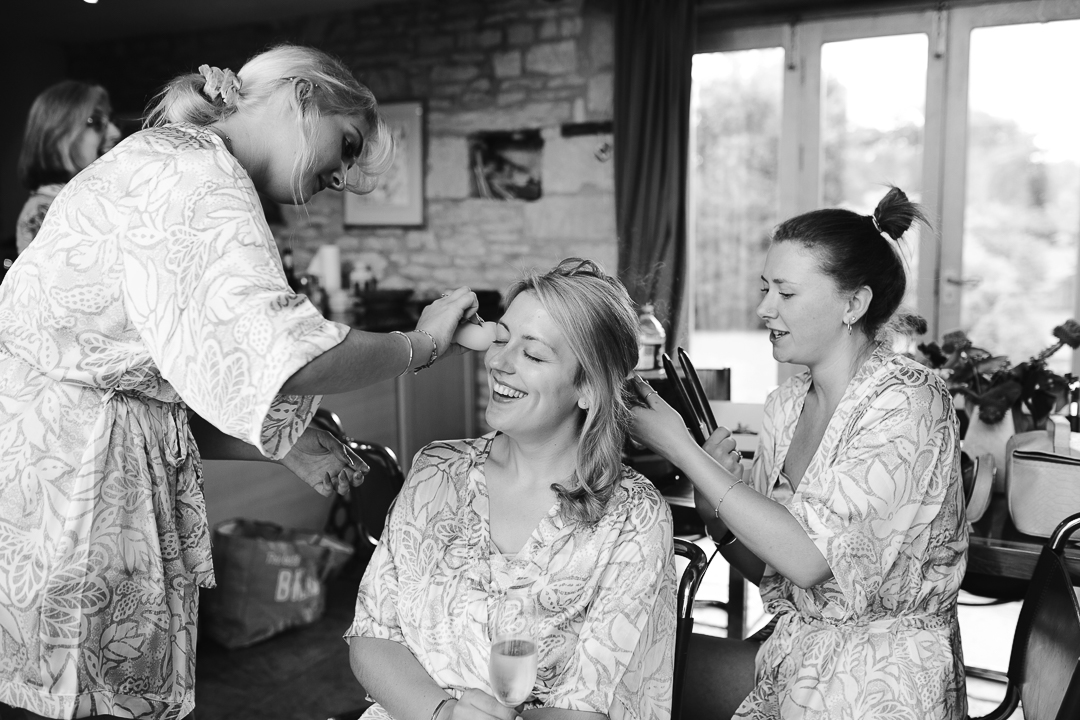 black and white natural photo of bride having hair and make up done on the morning of her wedding