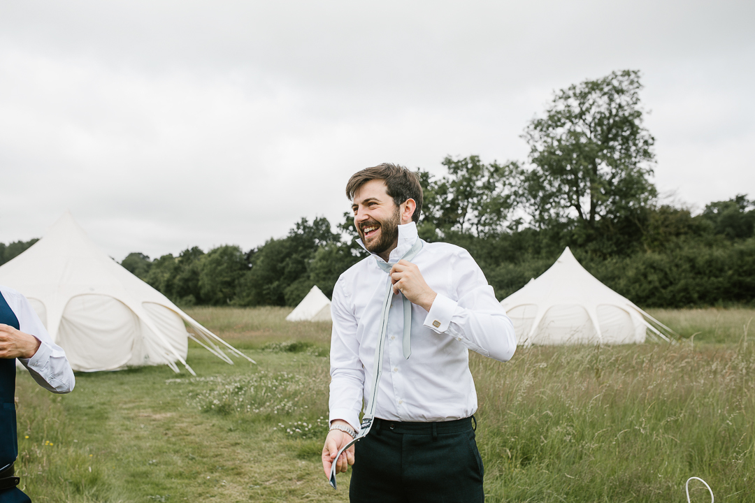 groom getting dressed for his wedding outdoors at his summer wedding in the cotswolds