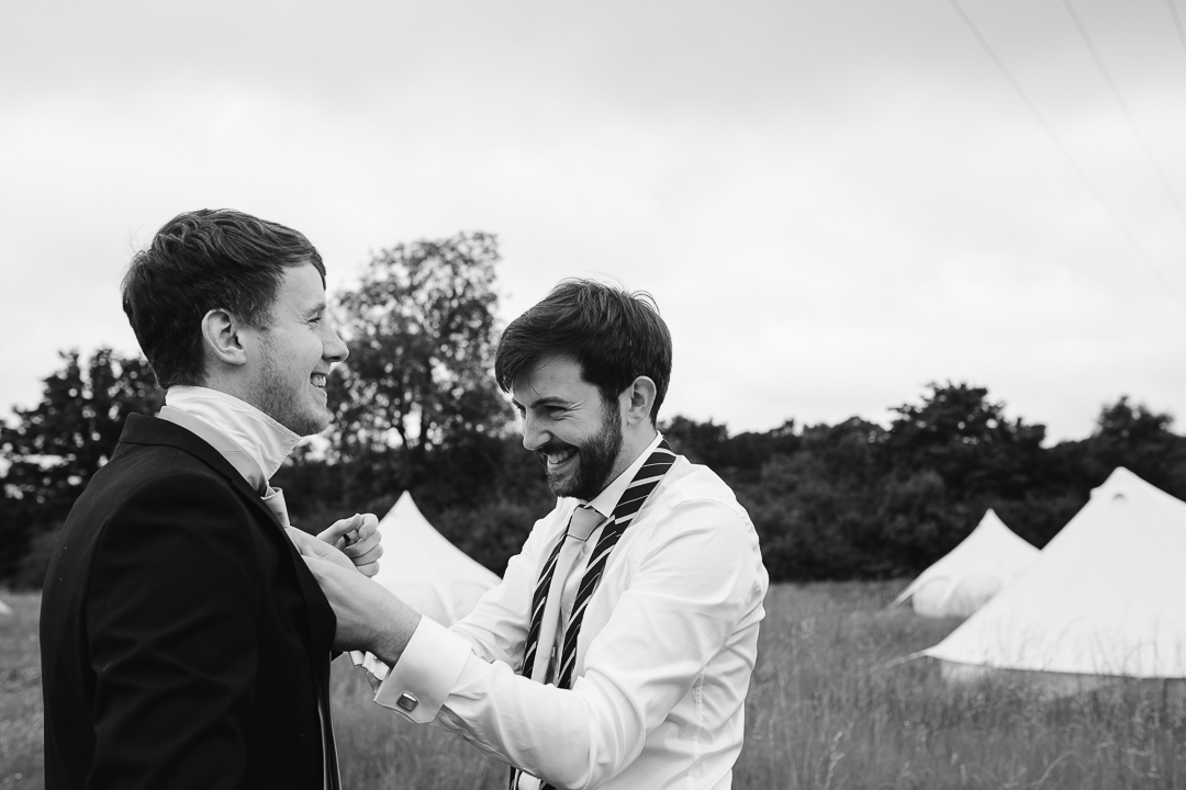 natural photo of groom laughing as his ties his friends tie