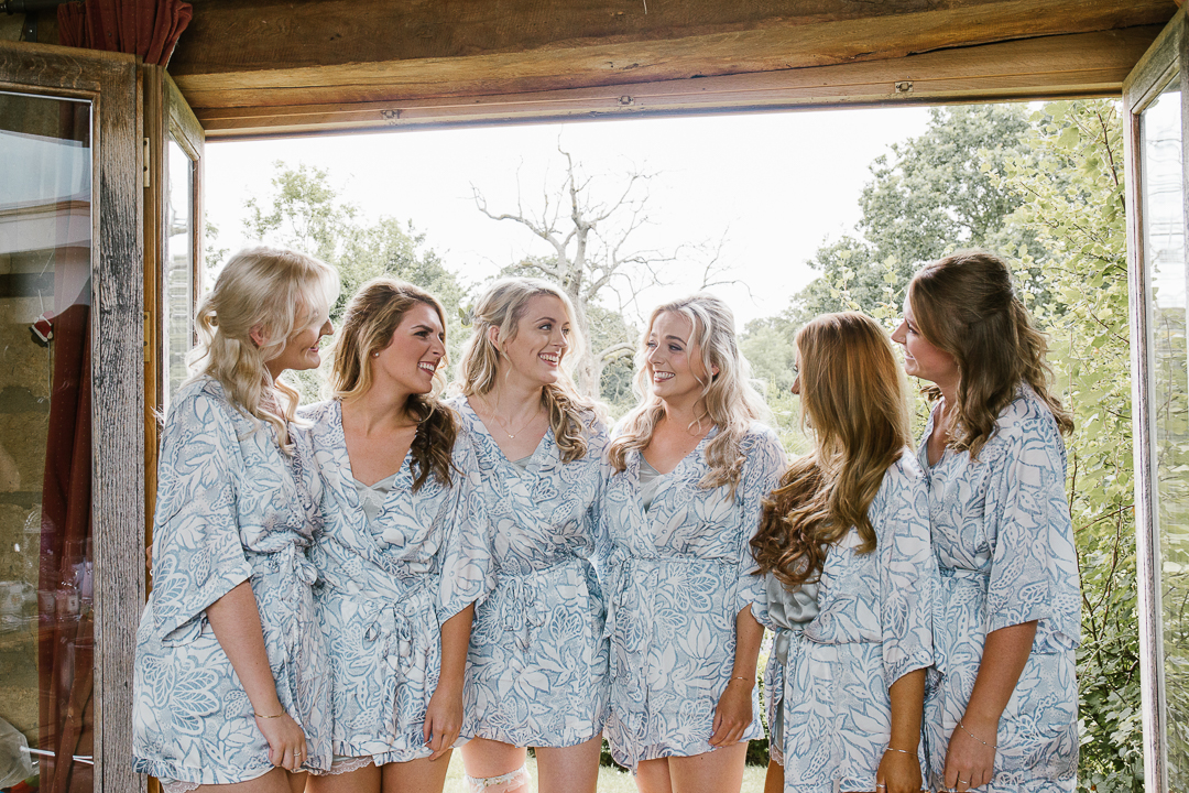 natural fun photo of bride with her bridesmaids on the morning of her wedding in matching robes