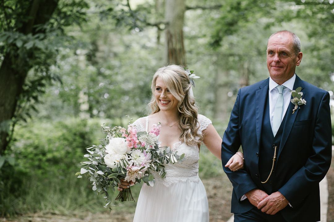 boho bride with father of the bride happily walking down the aisel in their outdoor woodland ceremony