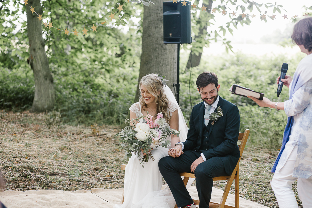 bride and groom laughing during a reading in their woodland outdoor wedding ceremony