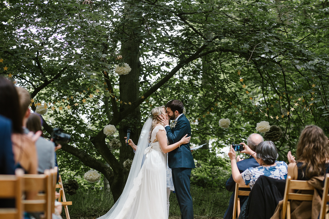 happy photo of the bride and groom having their first kiss