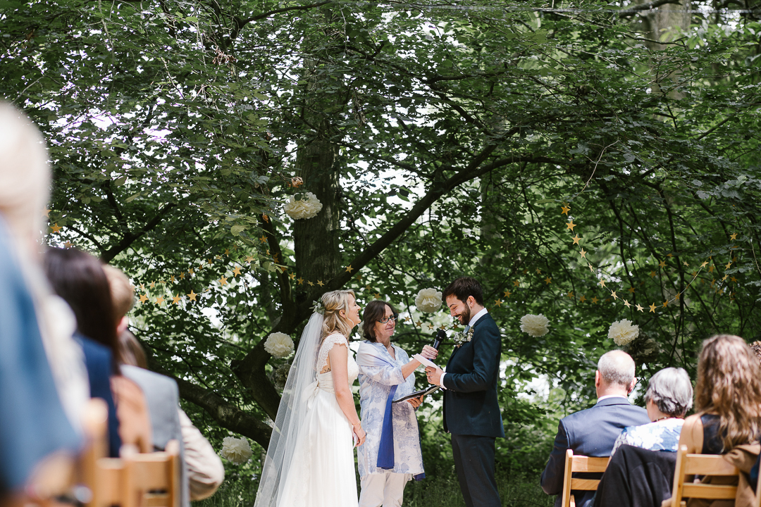 view from down the aisle of bride and groom reading their own vows in woodland wedding in the cotswolds- cotswolds wedding photographer