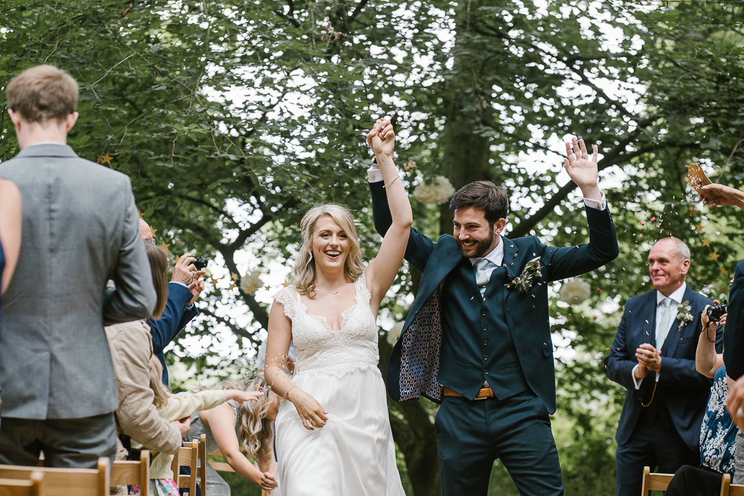 fun photo of the bride and groom waving their hands in the air after becoming husband and wife at their festival wedding in the cotswolds