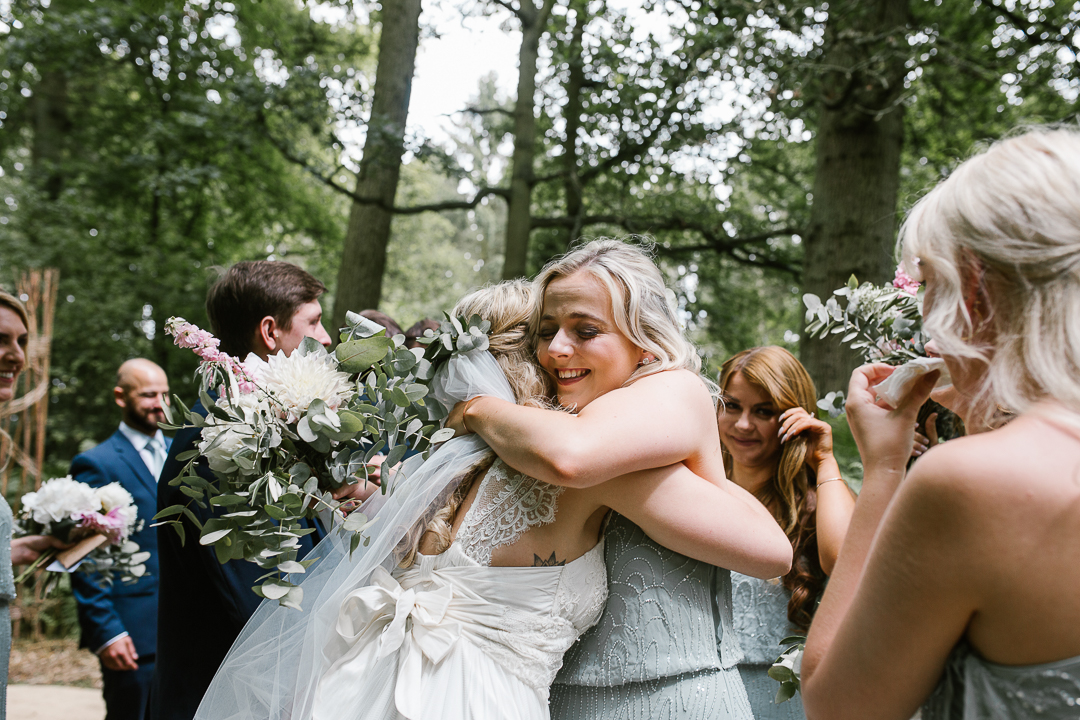 bridesmaid hugs bride after an emotional outdoor wedding ceremony