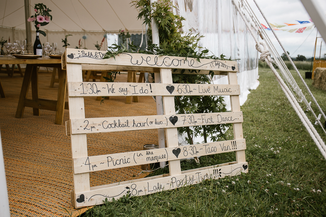 DIY order of service on a wooden palette at festival wedding