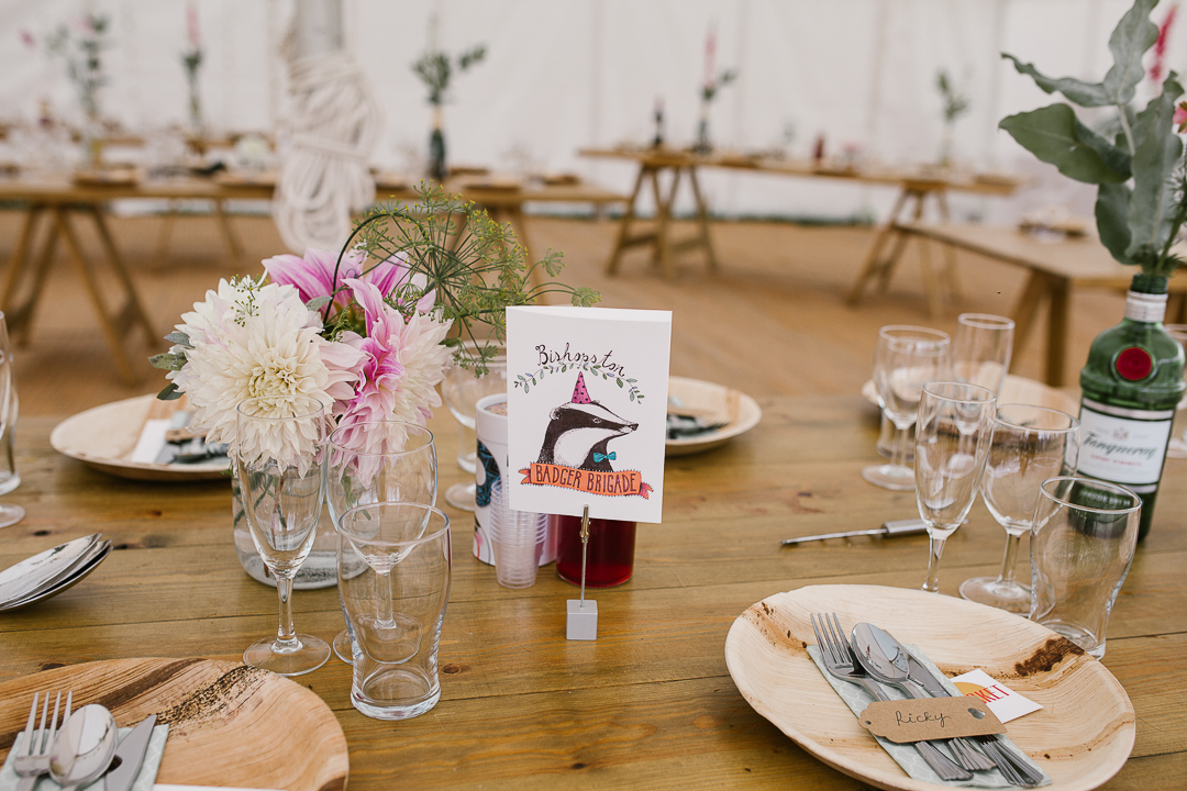 table wedding details featuring illustrated animals on wedding stationary, wooden plates and wild flowers- cotswolds wedding photographer