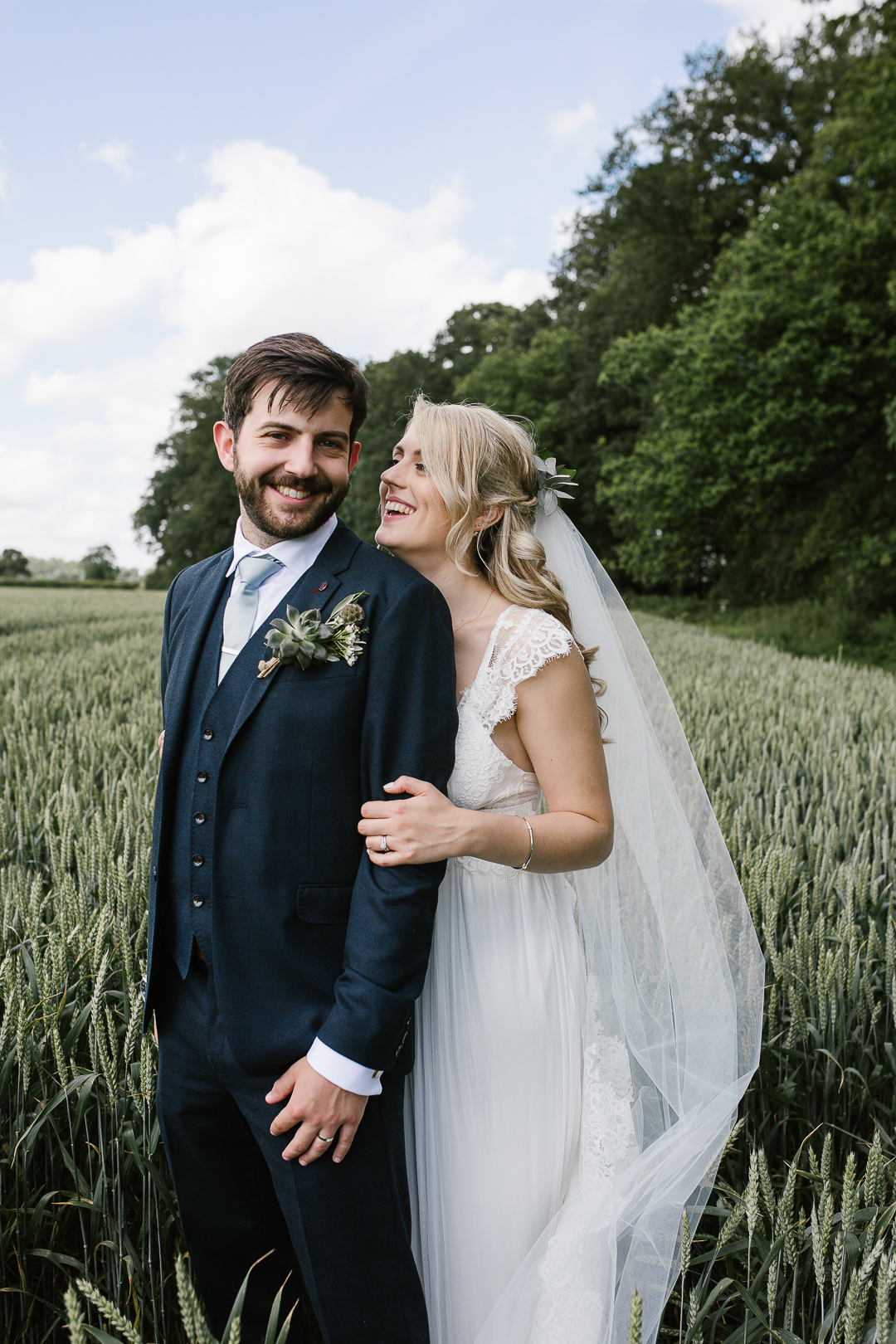 romantic photo of bride and groom laughing together in a field at wildwood bluebell in the cotswolds