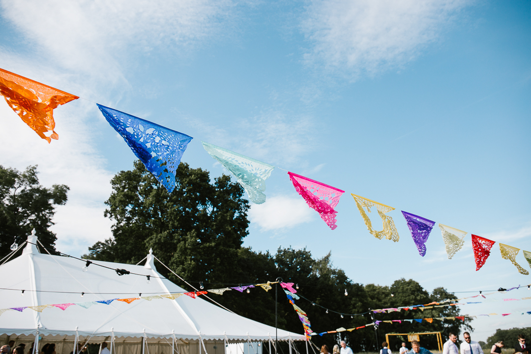 Mexican style bunting hanging at marquee wedding