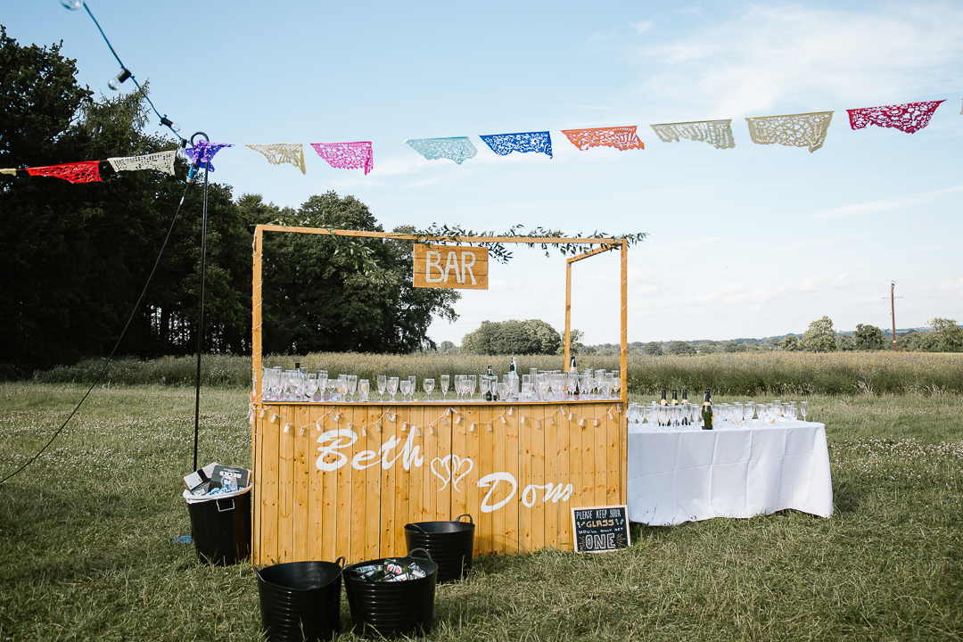 diy made wooden bar at outdoor festival themed cotswolds wedding