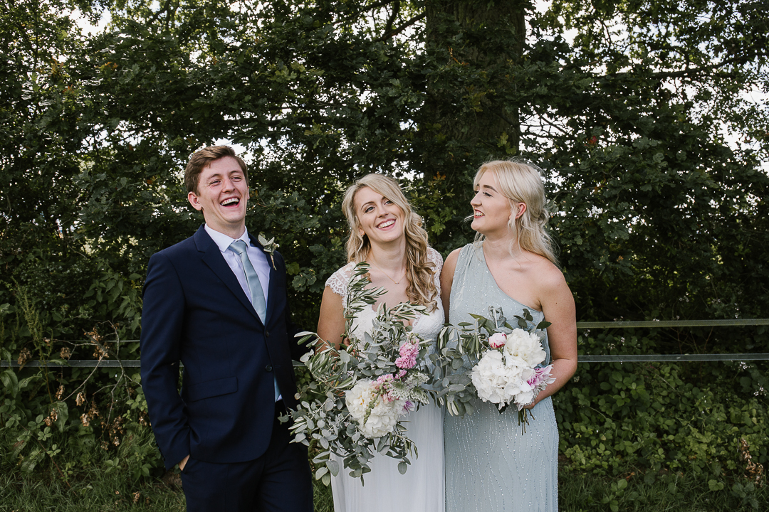 happy photo of bride with brother and sister laughing together in the cotswolds