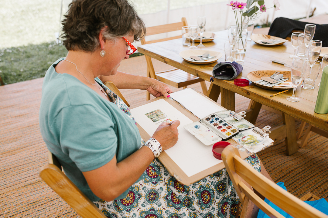 wedding guest painting a water colour of the woodland wedding in the marquee venue in the cotswolds