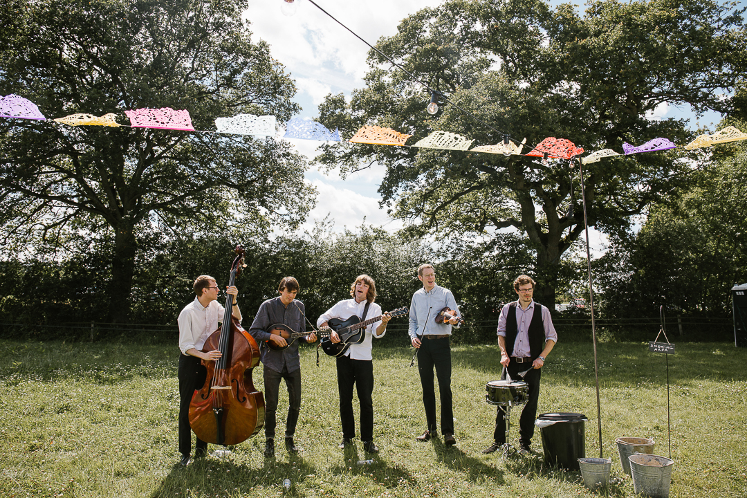 live band playing acoustic instruments at  a festival themed wedding
