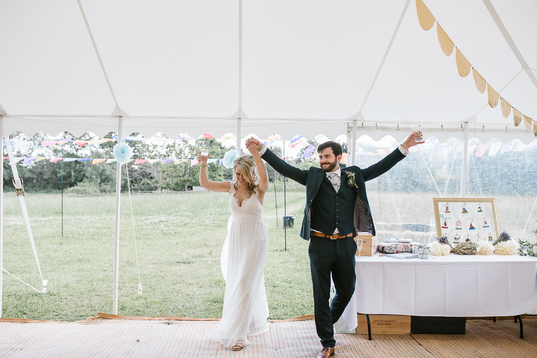 bride and groom celebrating as they enter their marquee wedding venue