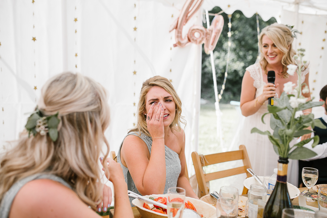 candid photo of bridesmaid crying during the brides wedding speech