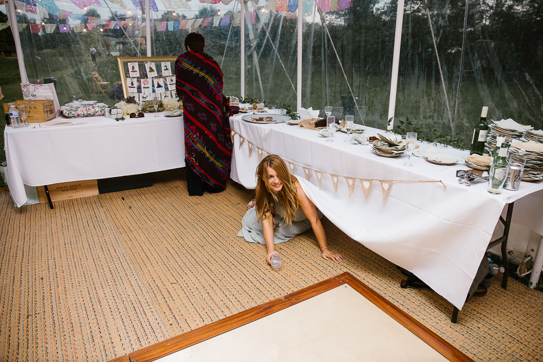 festival wedding, as a bridesmaid crawls drunk under the table at the wedding reception