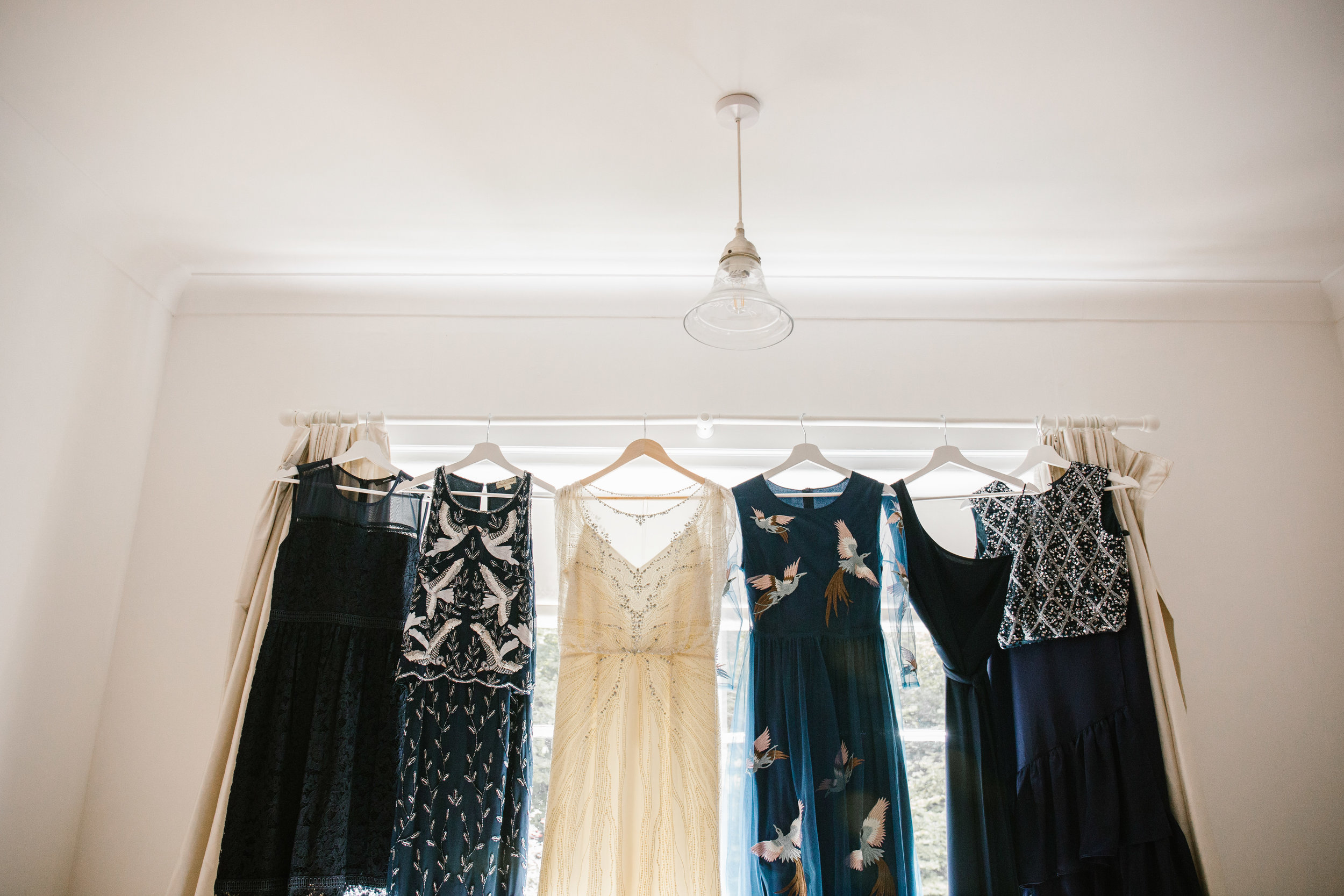 jenny packham wedding dress hanging with navy blue bridesmaids dresses