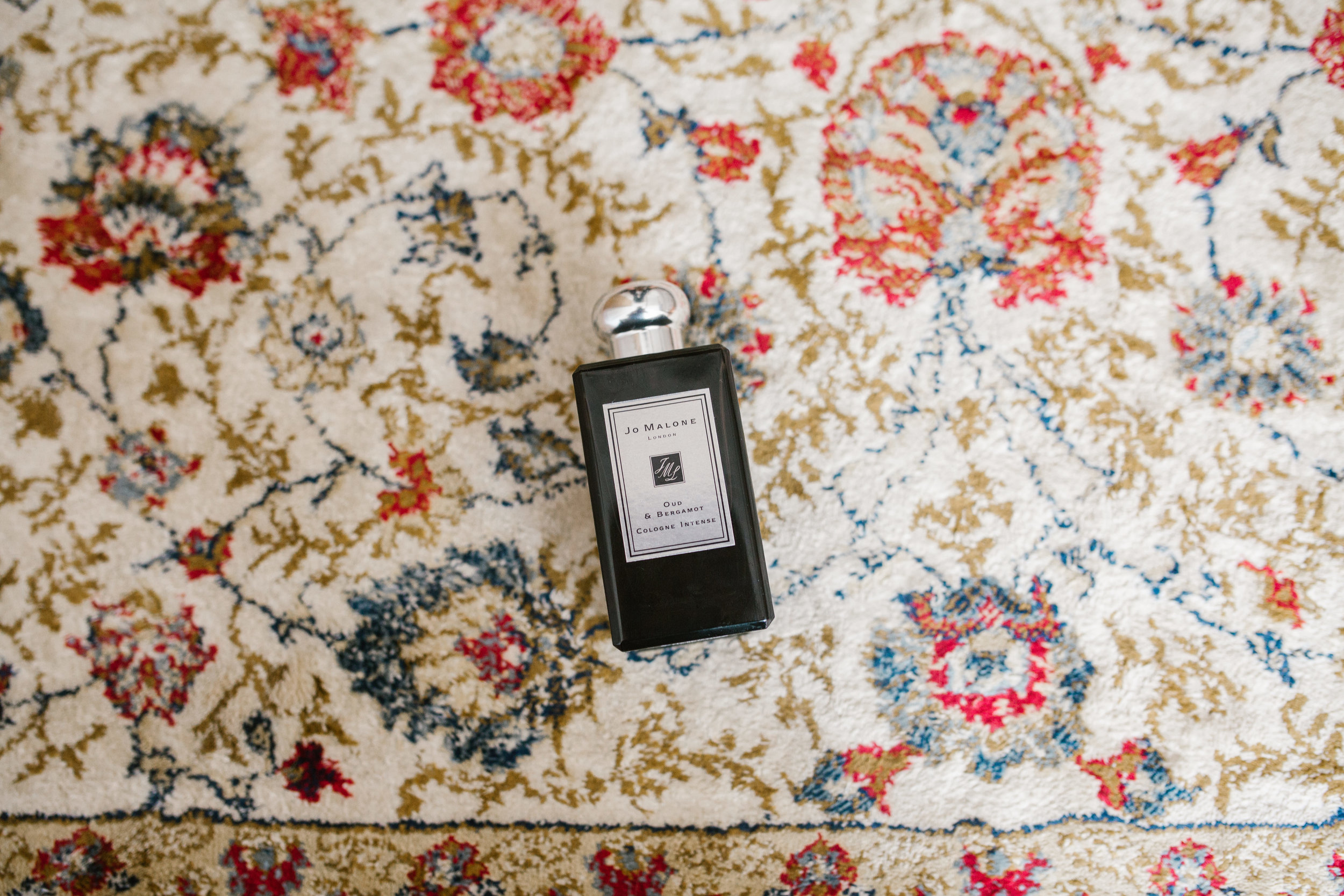 jo malone perfume on patterned carpet