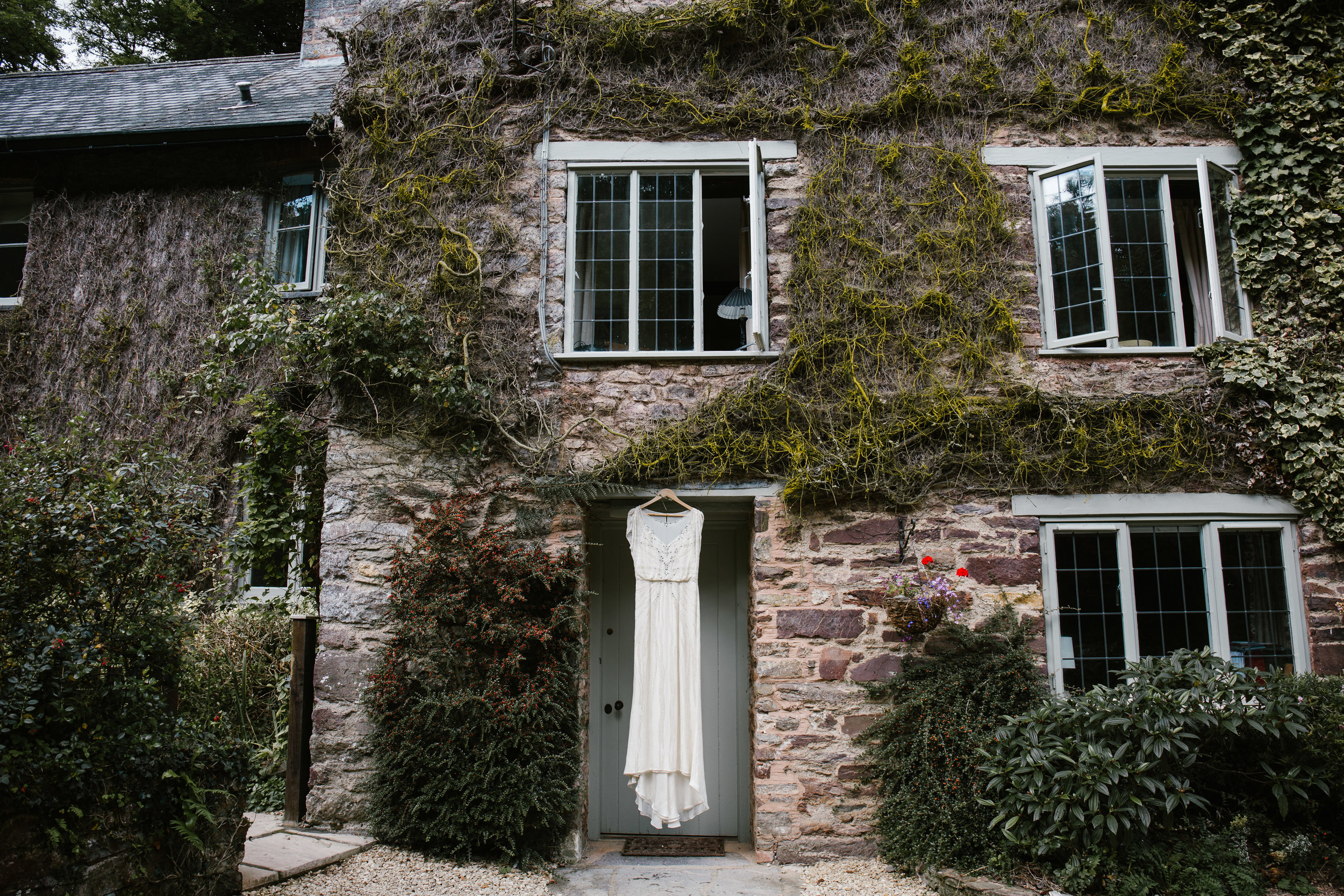 jenny packham dress hanging on a ivy covered cottage