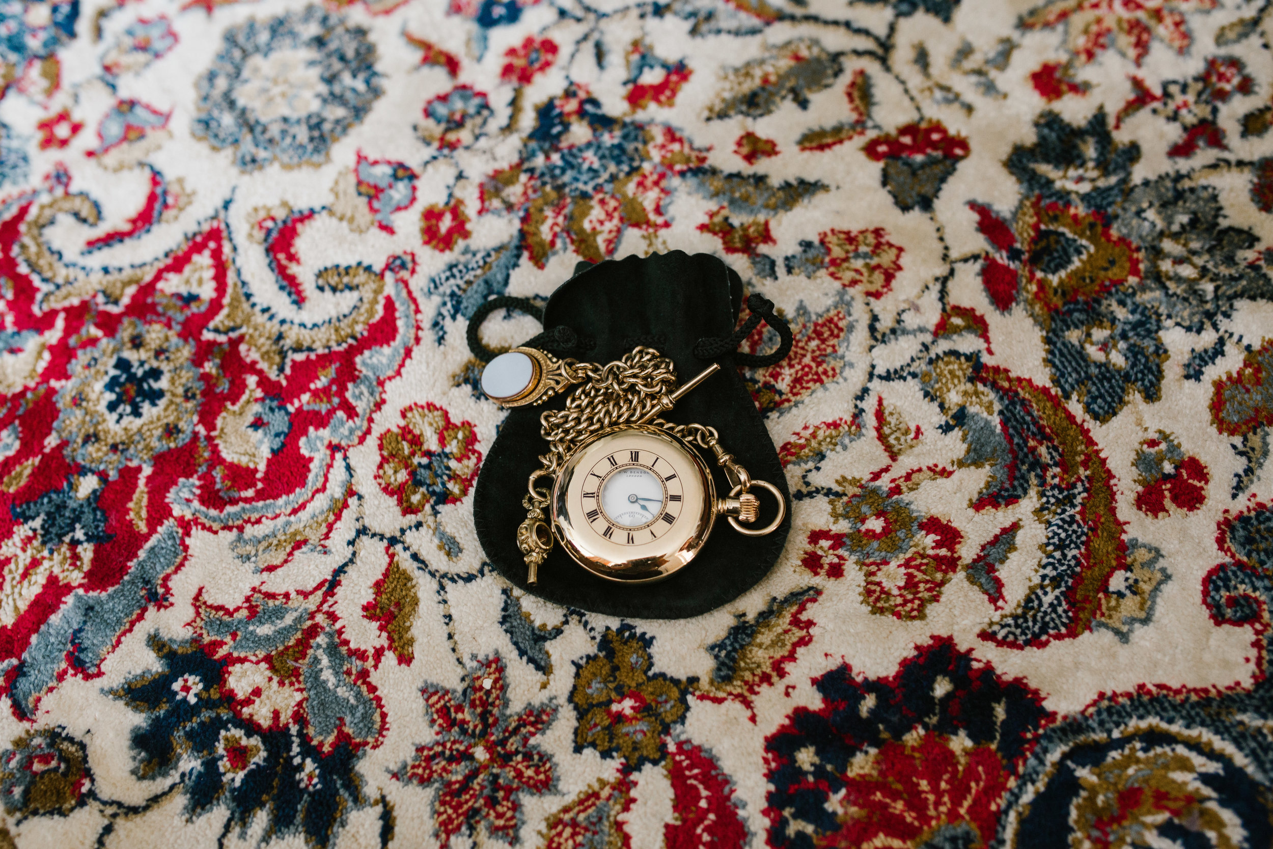 antique pocket watch on patterned carpet