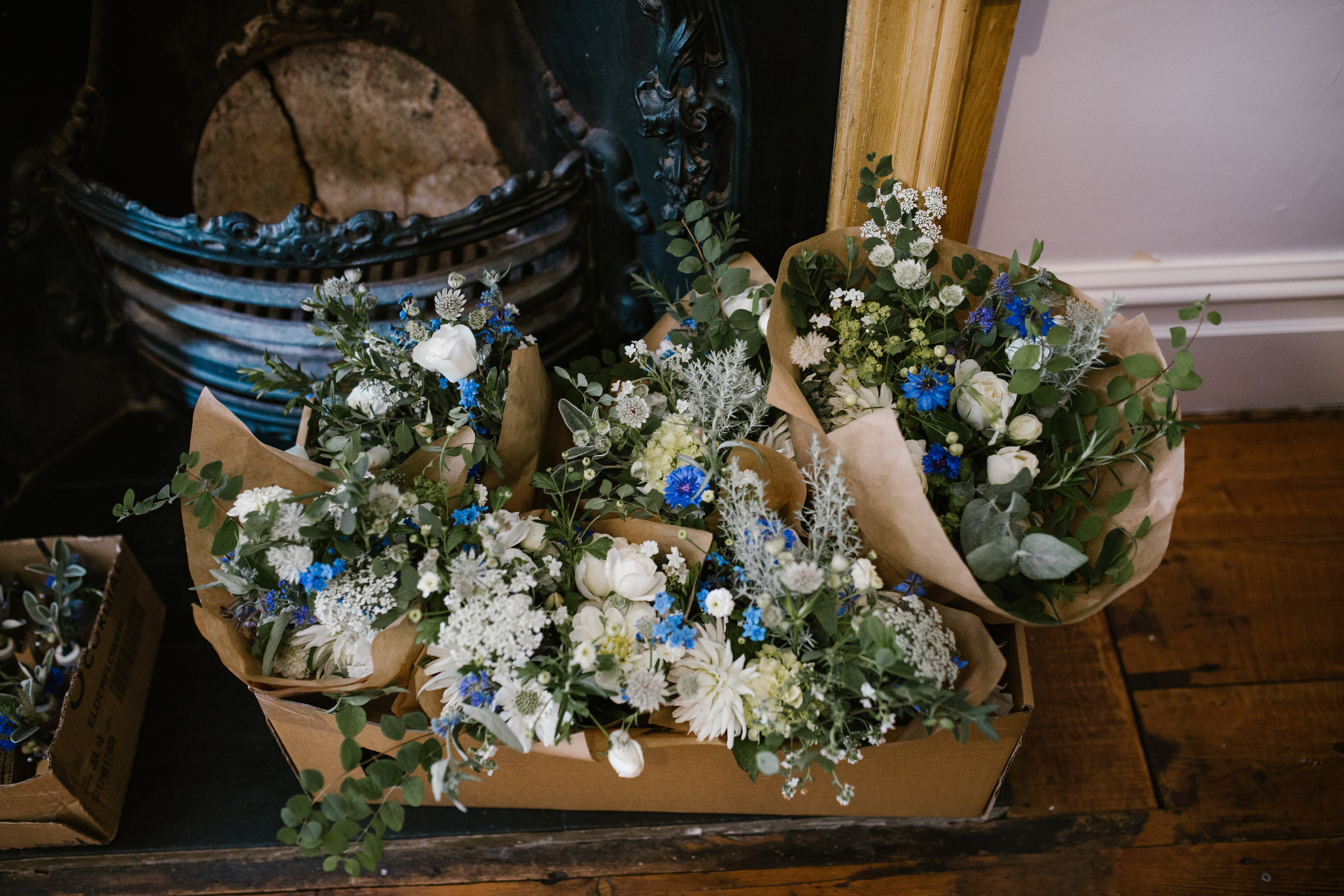 blue wild flowers wrapped in brown paper ready for an outdoor boho wedding