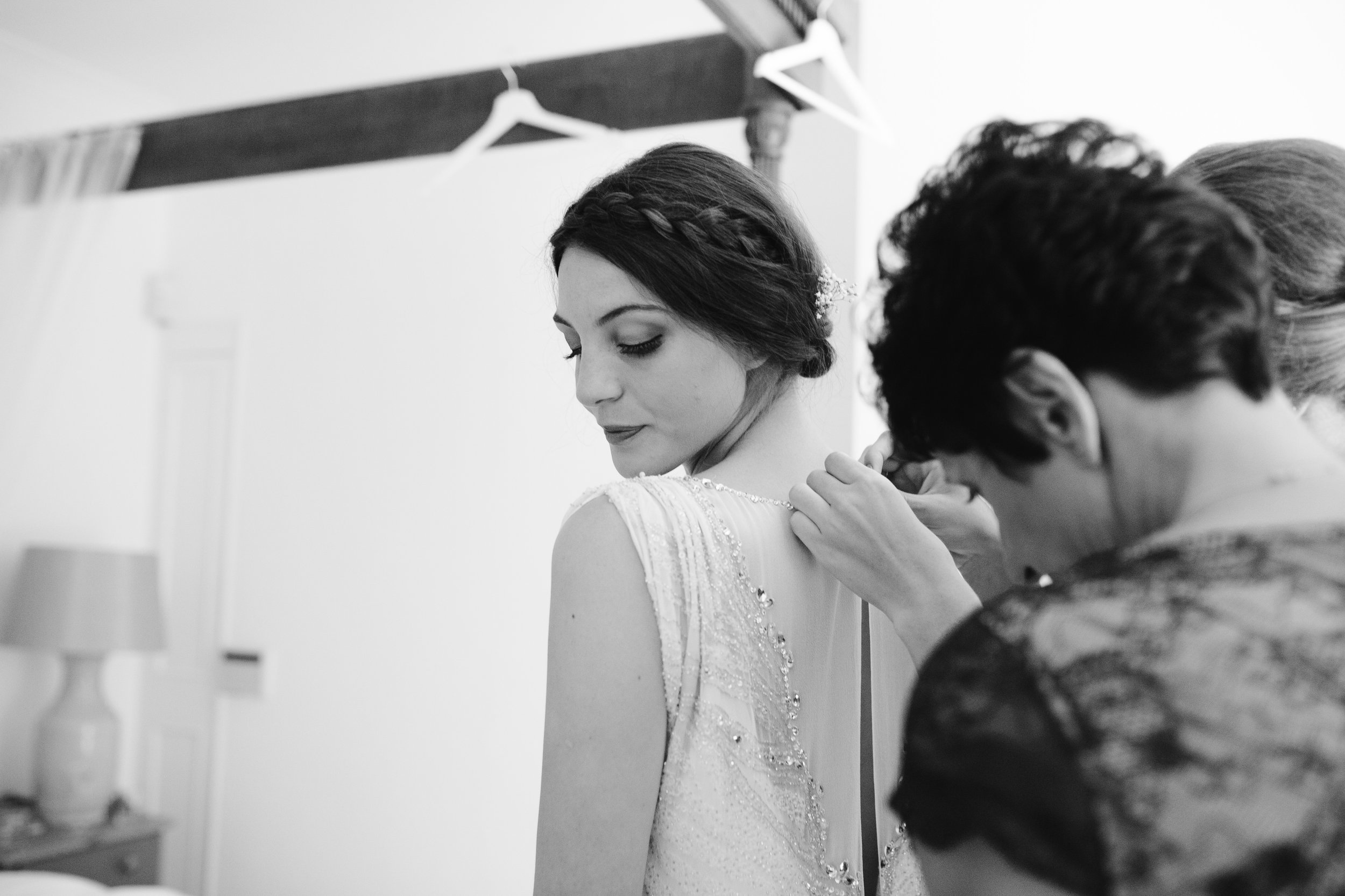 black and white photo of mother of the bride zipping up the jenny packham gown