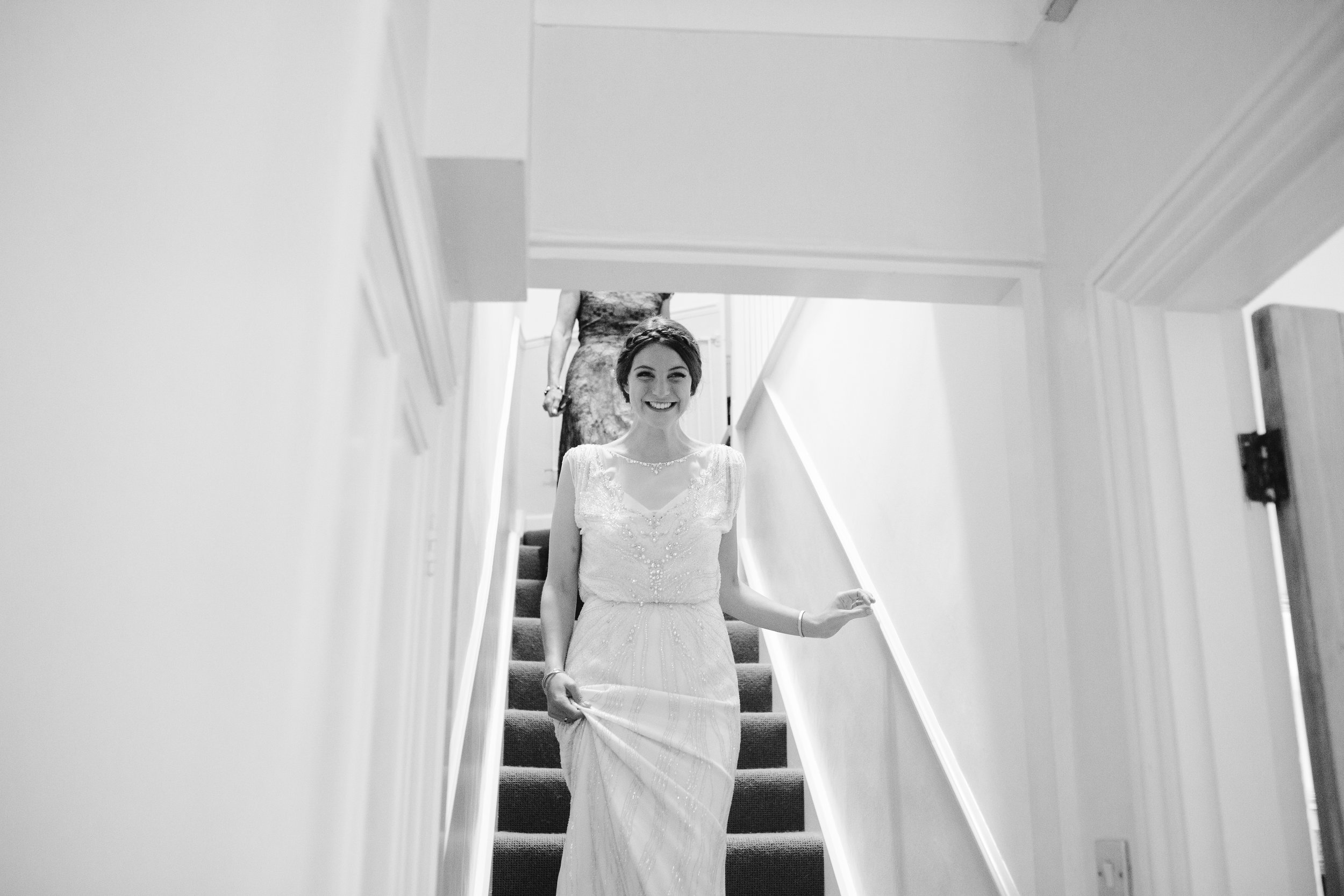 black and white photo of happy bride as she walks down the stairs towards her bridesmaids and dad