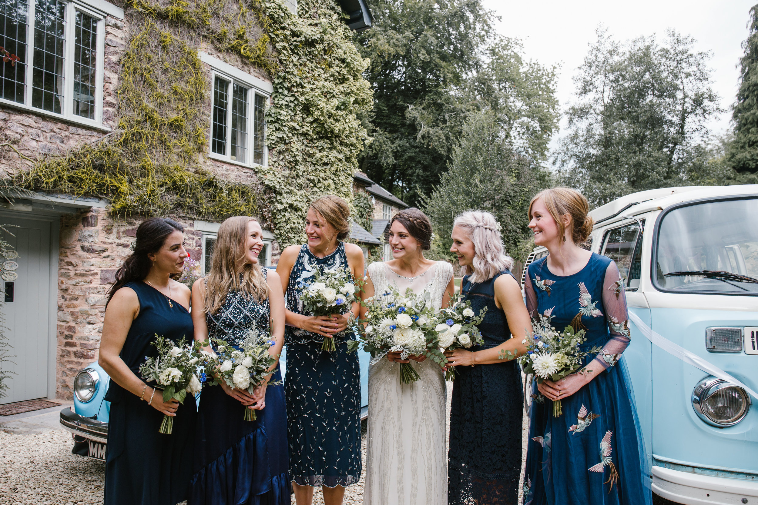 natural photo of bride and bridesmaids laughing together before the outdoor wedding ceremony