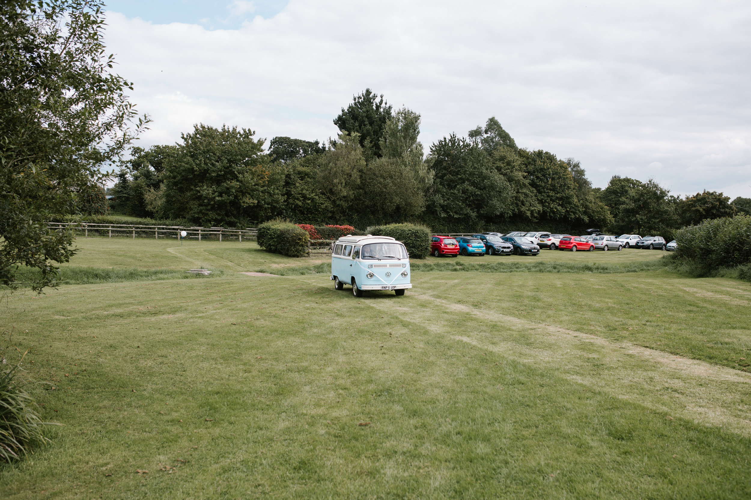 light vw campervan arriving at back garden wedding ceremony