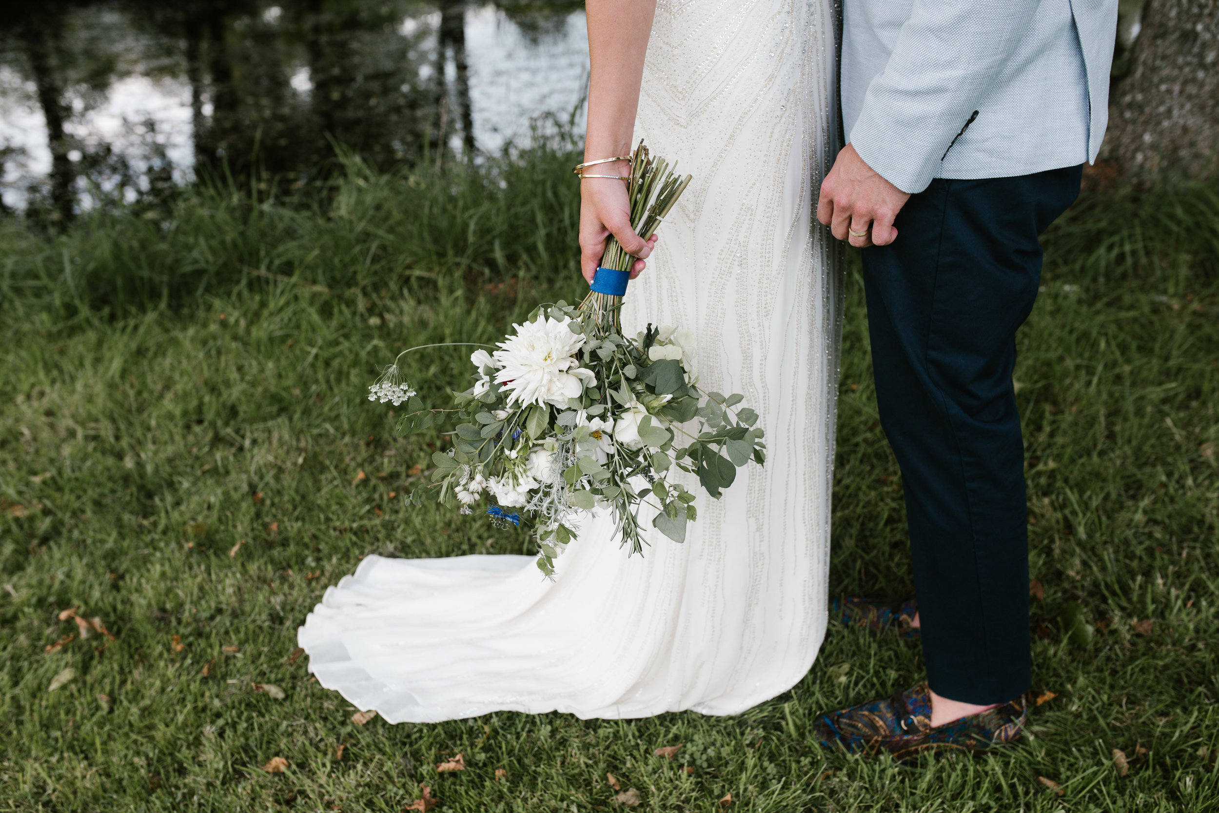 close up shot of wild blue flowers and jenny packham wedding gown