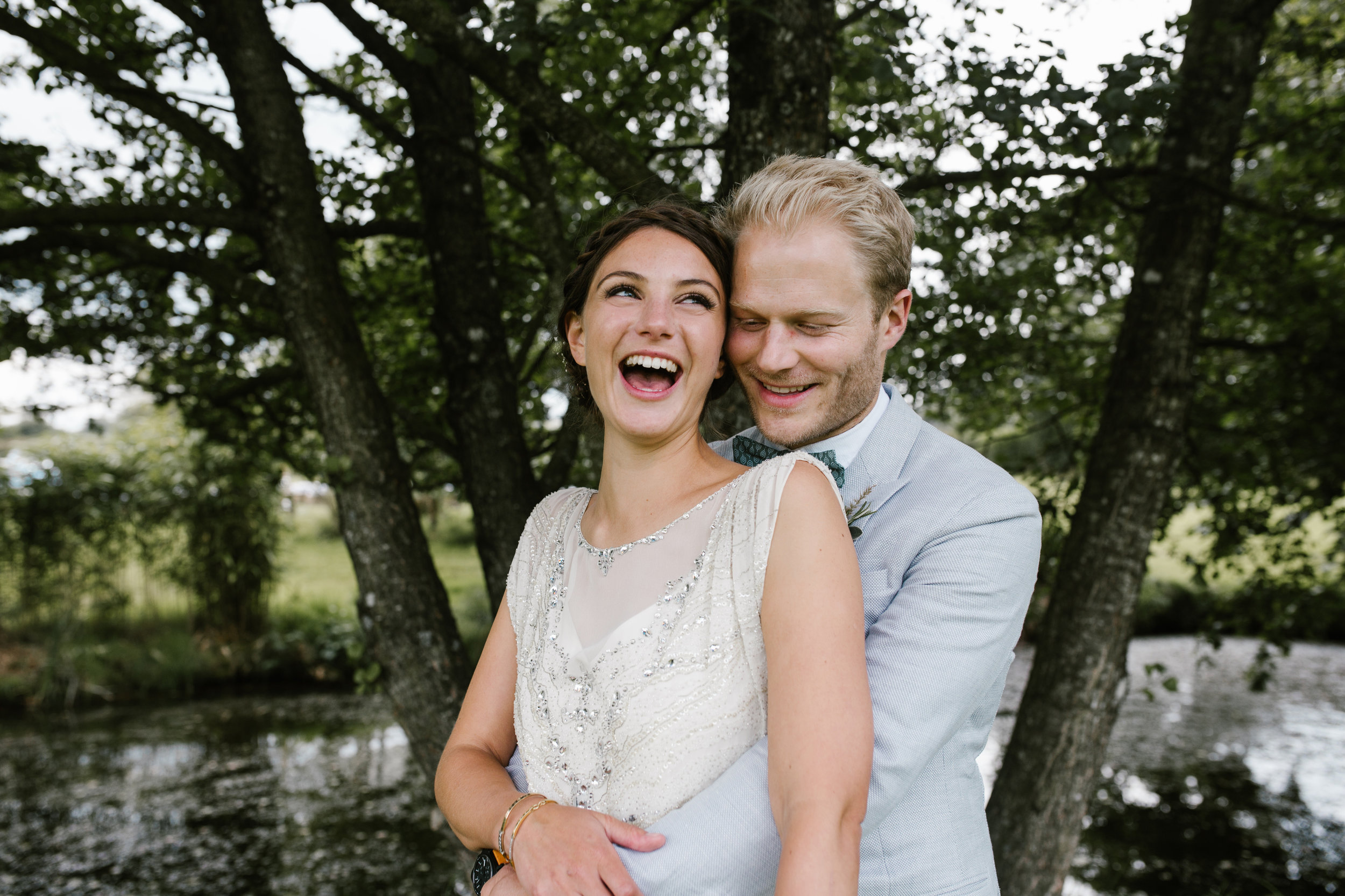 happy fun photo of bride and groom holiding each other close and laughing together