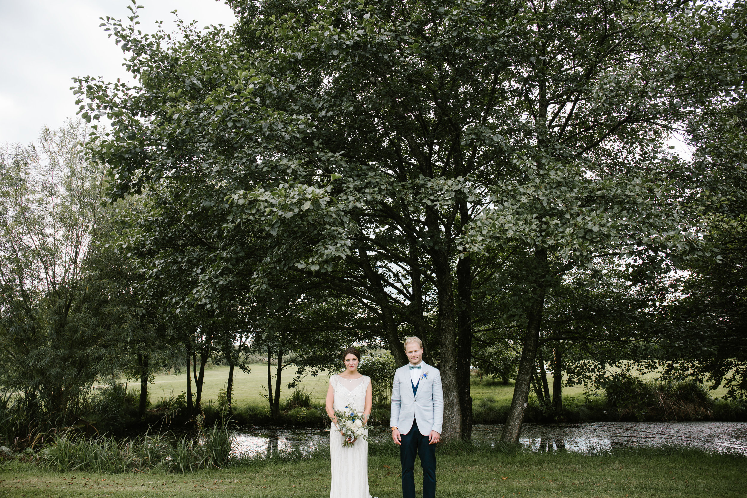 quirky photo of bride and groom stood together in the back garden of where they got married